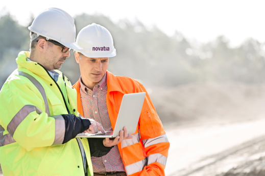 two men outside in hi viz with hats and laptop